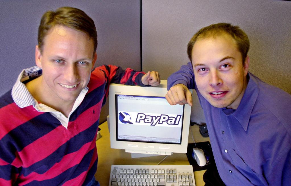 El director ejecutivo de PayPal, Peter Thiel, a la izquierda, y el fundador Elon Musk, a la derecha, posan con el logotipo de PayPal en la sede corporativa en Palo Alto, California, el 20 de octubre de 2000. Paul Sakuma — AP
