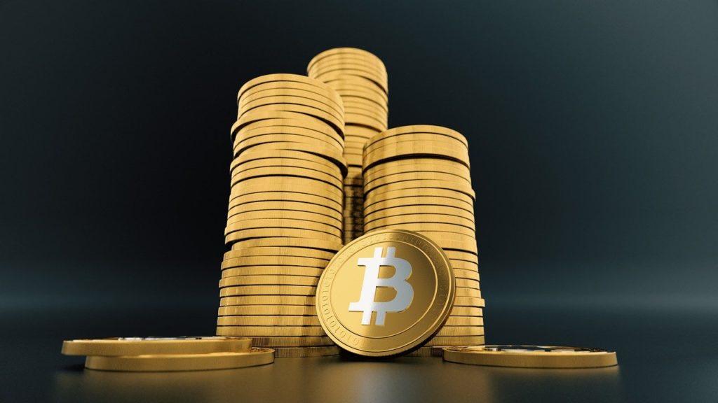 Imagen de tres montones de criptomonedas con el símbolo de Bitcoin