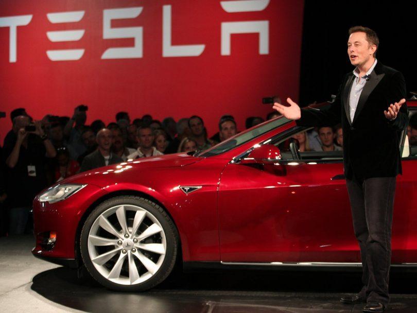 Fotografía de Elon Musk junto a un coche Tesla.