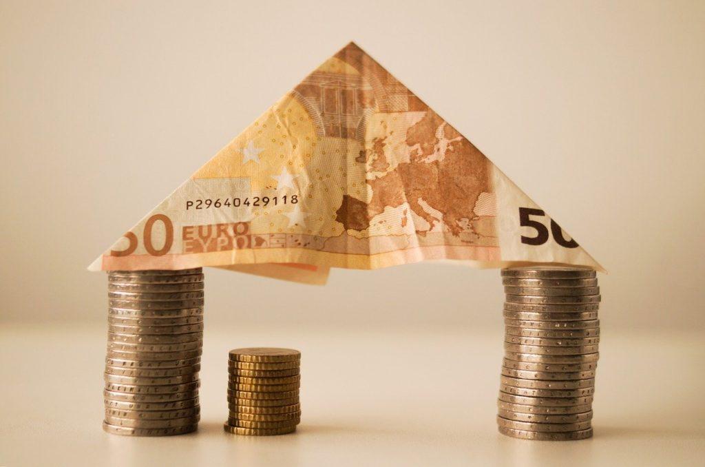 Tres torres de monedas de dos euros y 10 céntimos y un billete de 50 euros doblado.
