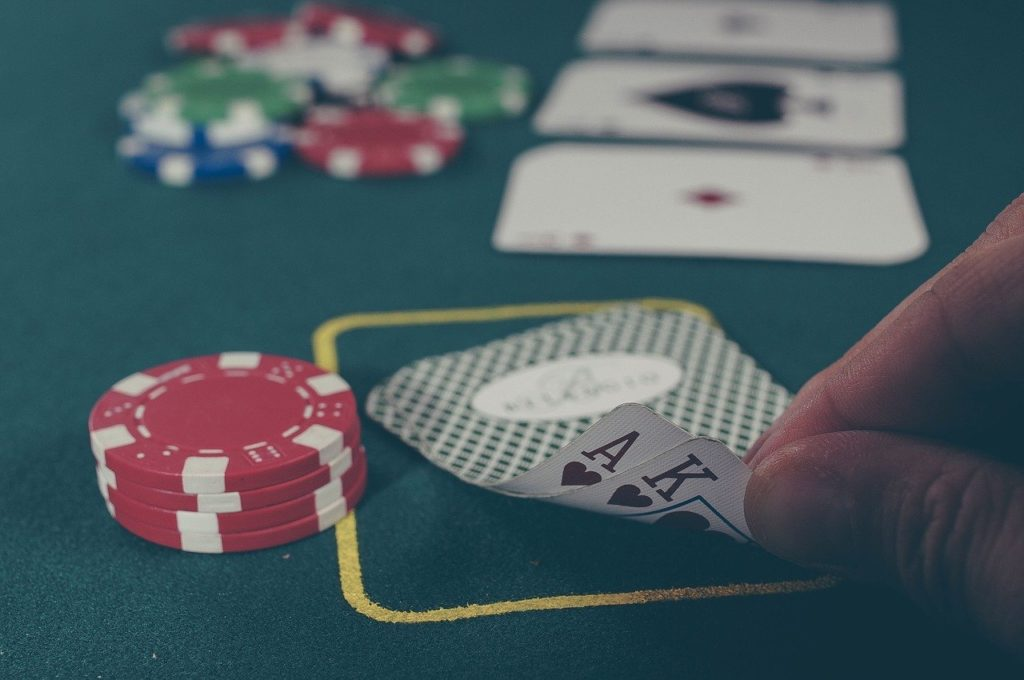 Imagen de una jugada de póker en un casino, en la que aparecen unas cartas y un montón de fichas.