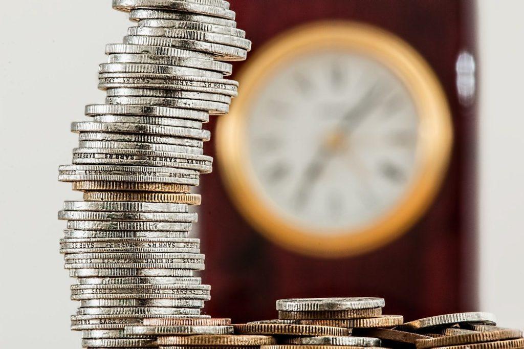 Torre de monedas con un reloj de pared al fondo.