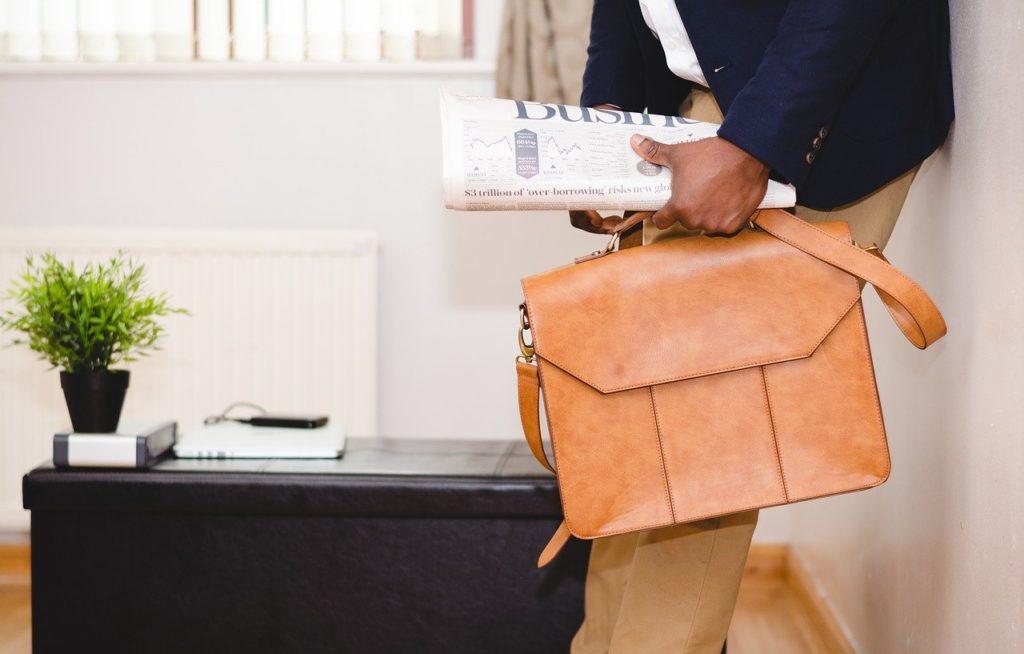 Hombre sujetando maletín y periódico.